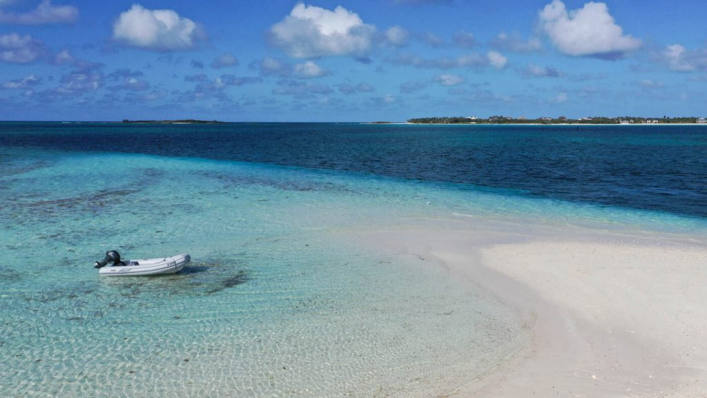 Inflatable dinghy anchored by island in Bahamas